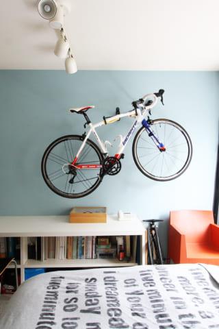 水色の壁と、ロードバイクのある寝室。