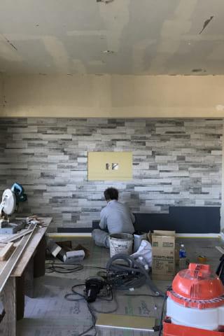 グレーのタイルの壁と、グレーの壁紙の壁。工事進行中。